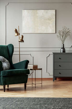 Emerald green wing back chair with pillow in grey living room interior with wooden commode