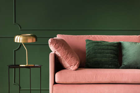 Emerald green pillows on pastel pink couch in stylish living room interior with dark green wall