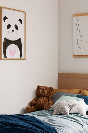 Teddy bear on single wooden bed in blue and orange bedroom interior Stockfoto