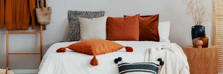 Decorative pillows on a bed in a scandi bedroom interior. Real photo 스톡 콘텐츠