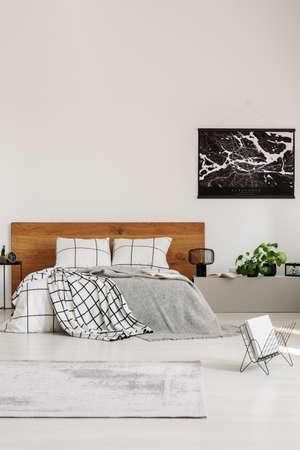 Espace de copie sur mur blanc avec carte noire dans une chambre moderne avec lit king size avec tête de lit en bois Banque d'images