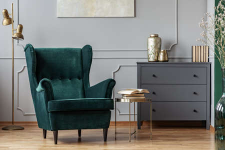 Books on stylish golden small table next to emerald green velvet wing back chair in grey living room interior