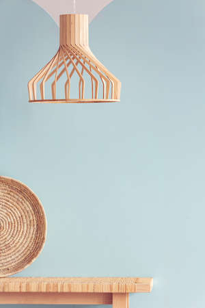 Wicker chandelier above wooden bench in simple natural blue interior