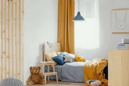 White, wooden, blue and orange design in bright bedroom interior