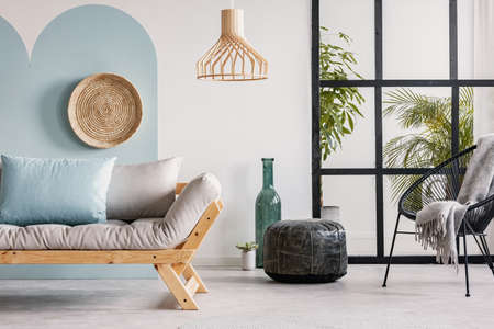 Classy living room interior with scandinavian futon sofa, pouf, armchair and urban jungle