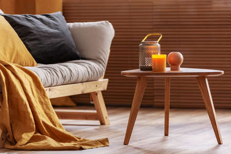 Orange candle on wooden coffee table in cozy living room interior Stockfoto
