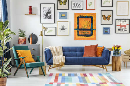 Green armchair next to blue settee in colorful living room interior with painting and posters. Real photo