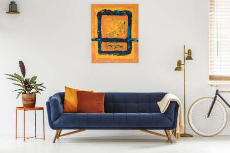 White living room interior with royal blue lounge, modern art painting, gold lamp, fresh plant on metal table and bike under window with blinds Stockfoto