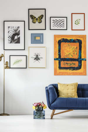 Fresh flowers in glass vase standing next to blue sofa with pillow in white living room interior with gallery on the wall