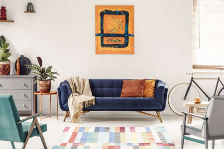 Yellow and navy blue painting above sofa in modern living room interior with bike. Real photo