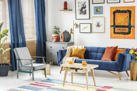 Bright and cozy living room interior with blue drapes, a sofa with orange cushions, gray armchair and a wooden table with two cups of coffee. Real photo