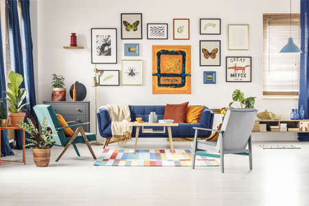 Simple posters gallery hanging on the wall in bright living room interior with blue sofa, two armchairs, fresh plants and wooden coffee table standing on colorful carpet