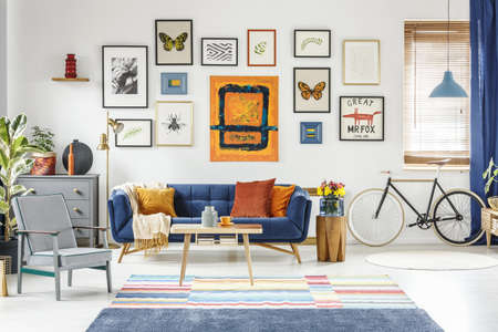 Grey armchair and blue sofa in spacious living room interior with posters and bicycle. Real photo Stockfoto