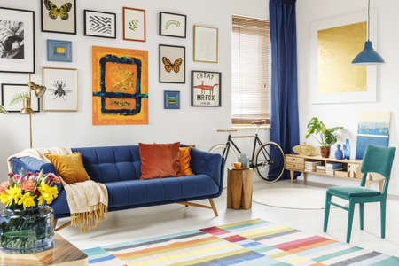 Spacious living room interior with a blanket and orange pillows on a blue sofa, green chair, colorful rug and gallery of posters and painting on white wall. Real photo Stockfoto