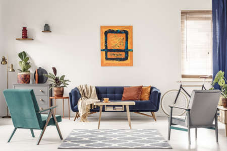 Real photo of a navy blue sofa with orange cushions and an artwork above in bright and spacious living room interior with two retro armchairs Stockfoto