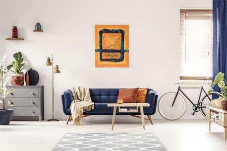 Pintura amarilla y azul colgada en una pared blanca en el interior de la luminosa sala de estar con armario gris, lámpara dorada, sofá con manta y almohadas y bicicleta de pie debajo de la ventana con persianas