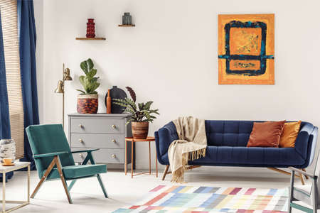 Orange end table with fresh plant standing next to navy couch with blanket and pillows in white living room interior with painting, green armchair, vases on shelves and colorful carpet on the floor