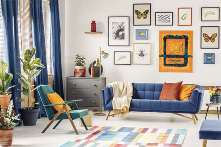 Orange pillow on green armchair near blue couch in colorful living room interior. Real photo