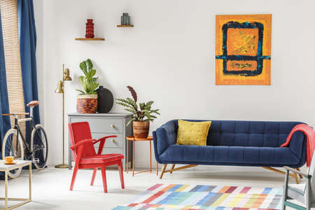 Red chair and royal blue lounge placed in bright sitting room interior with colorful carpet, modern art painting, fresh plants and gold lamp next to grey cupboard Stockfoto