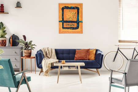 Yellow and navy blue painting above sofa in colorful living room interior with bike. Real photo