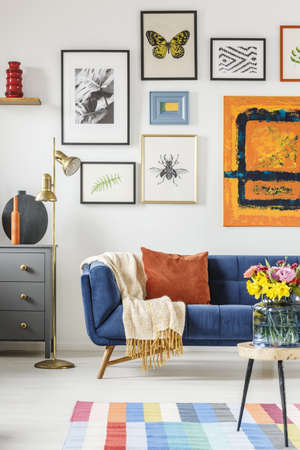 Blanket and pillow placed on navy blue couch standing in white living room interior with many posters and gold lamp Stockfoto
