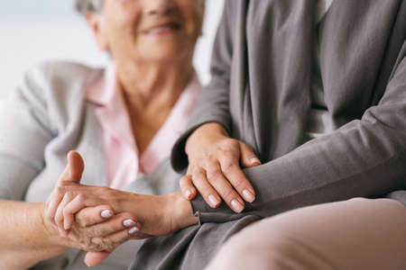Close up of older woman's and caregiver's hands Stock Photo