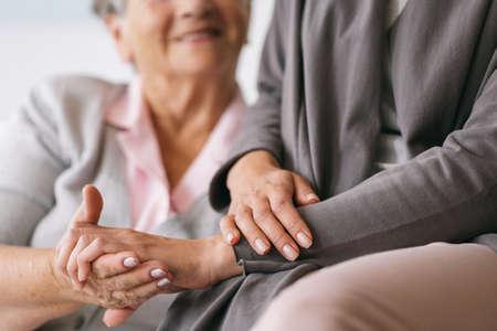 Nahaufnahme der Hände einer älteren Frau und einer Pflegekraft
