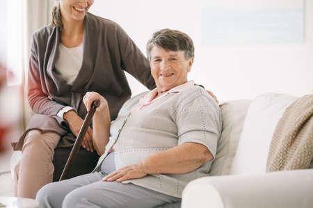 Oudere gehandicapte vrouw met stok in verpleeghuis met conciërge Stockfoto