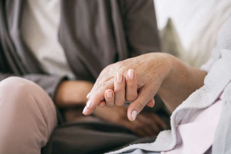 Close up of caregiver holding older womans hand Zdjęcie Seryjne
