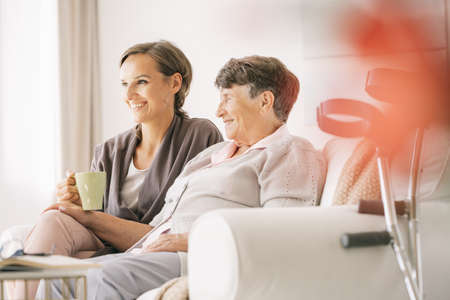 Older disabled woman spending time with her nurse