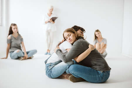 Two teenage girls hugging each others on a therapy
