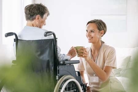 Senior lady on a wheelchair ad her helpful nurse serving the tea