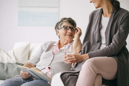 Older woman reading a book together with young caregiver