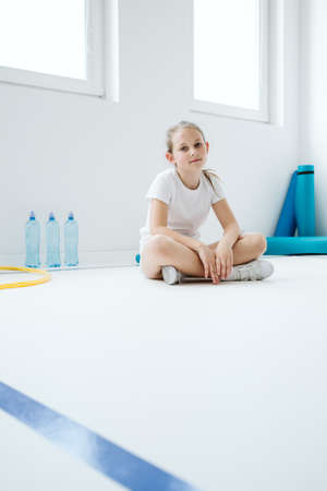 Young tired girl sitting on the floor after training Stockfoto
