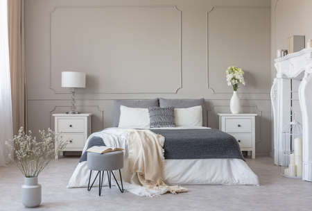 Flowers on nightstand table in delightful bedroom interior with grey and white design