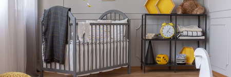 Panoramic view of cute yellow and grey baby bedroom with grey crib and black shelf with book, toys, blankets and clock