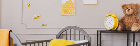 Panoramic view of cute yellow and grey baby bedroom with teddy bear and clock on black wooden shelf Banco de Imagens