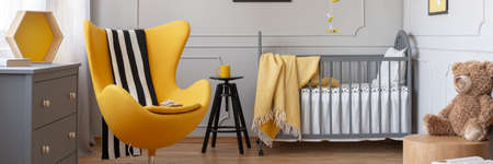 Panoramic view of cute yellow and grey baby bedroom with fashionable egg chair, wooden commode and crib