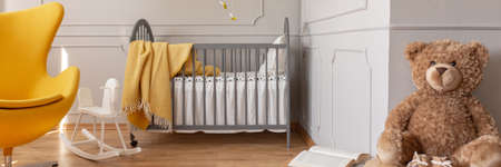 Panoramic view of cute yellow and grey baby bedroom with teddy bear, rocking horse, egg chair and crib with blanket
