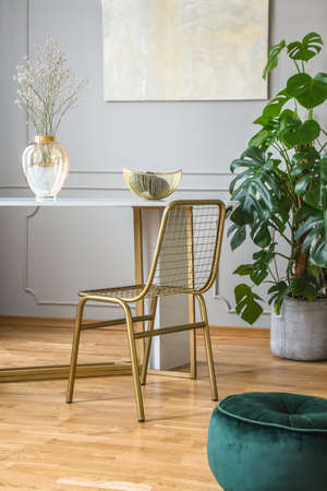 Fancy golden chair at small dining table in chic living room