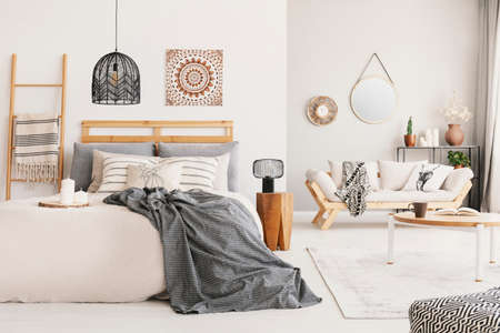 Warm ethno living room and bedroom with beige scandinavian settee and king size bed with grey blanket, real photo Stock Photo