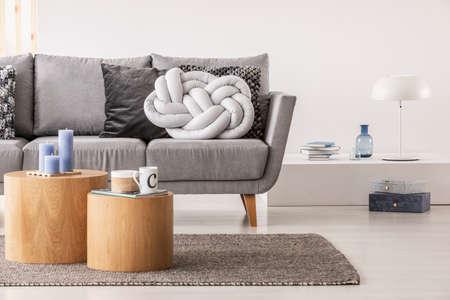 Trendiges hellgraues Kissen mit Knoten auf bequemer skandinavischer Couch