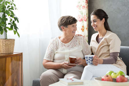 Happy senior lady sitting on couch, holding cup of tea and smiling to beautiful volunteer at nursing home Stockfoto