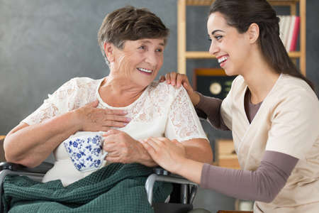 Positive senior lady in wheelchair holding cup of tea and smiling to beautiful volunteer at nursing home