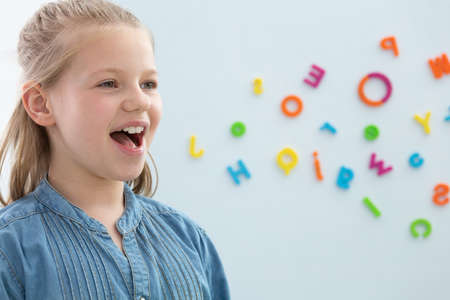 Cute blond little girl opening her mouth during speech therapy, copy space on the wall with letters Stockfoto