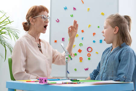 Cute blond little girl opening her mouth during speech therapy with senior professional therapist, copy space on the wall with letters