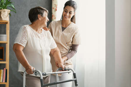 Smiling pretty nurse and disabled old lady with walker at home Stockfoto