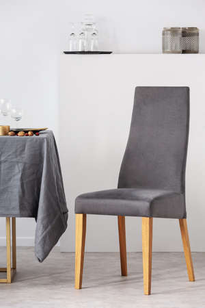 Vertical view of grey chair next to dining table in white interior