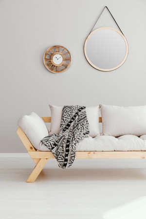 Round mirror and wooden clock on the empty wall of spacious living room interior with beige scandinavian sofa with patterned blanket , real photo
