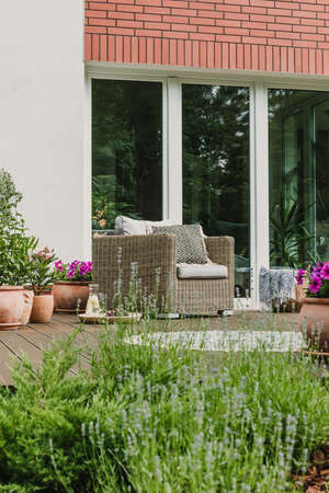 Comfy wicker armchair with pillows on wooden terrace of trendy suburban home 스톡 콘텐츠 - 129344066